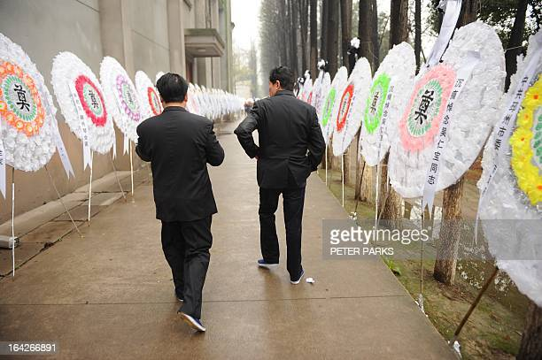To go with 'CHINASOCIALECONOMYPOLITICS' story by Bill Savadove Mourners walk past wreaths for dead retired Communist Party chief Wu Renbao at his...