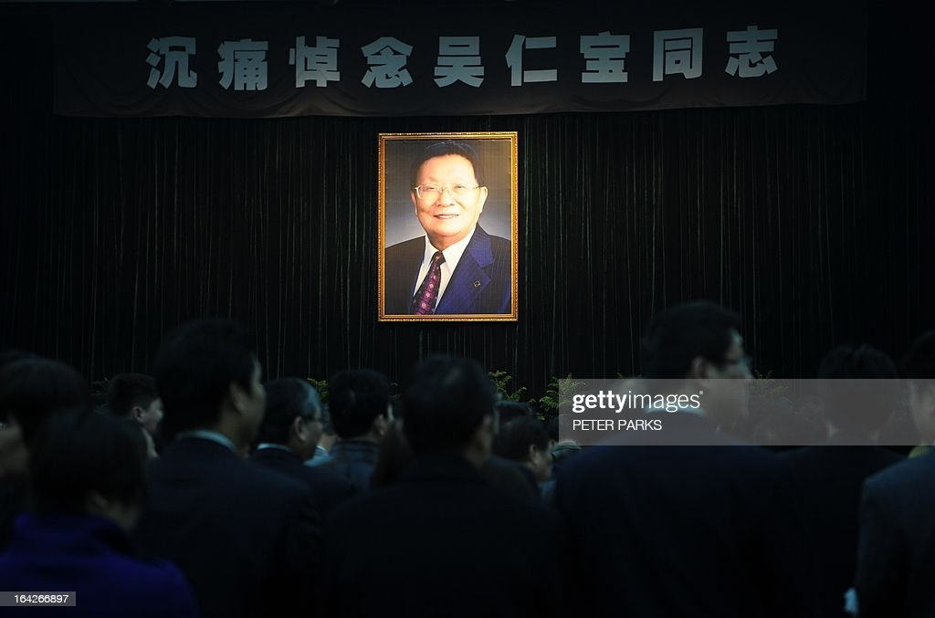 To go with 'CHINA-SOCIAL-ECONOMY-POLITICS' story by Bill Savadove Mourners gather in front of a photo of dead retired Communist Party chief, Wu Renbao at his funeral in the village of Huaxi on March 22, 2013. Residents of China's 'richest village' bid farewell to the man who made Huaxi a socialist paradise, with a 20-vehicle funeral procession transporting his coffin after he died on 18 March of cancer aged 84. AFP PHOTO/Peter PARKS