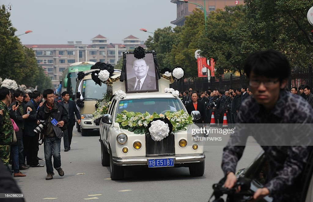 To go with 'CHINA-SOCIAL-ECONOMY-POLITICS' story by Bill Savadove The coffin with the body of retired Communist Party chief, Wu Renbao, is driven through the streets of the village of Huaxi on March 22, 2013. Residents of China's 'richest village' bid farewell to the man who made Huaxi a socialist paradise, with a 20-vehicle funeral procession transporting his coffin after he died on March 18 of cancer aged 84. AFP PHOTO/Peter PARKS