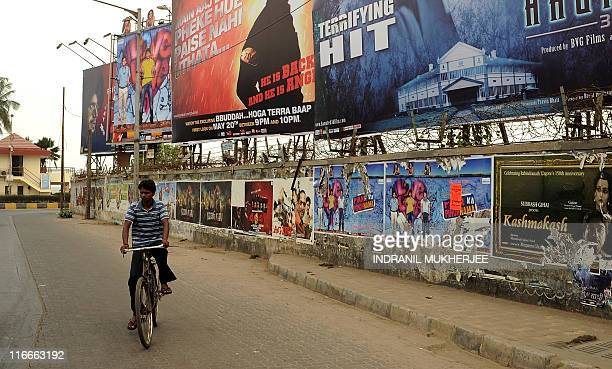 To go with EntertainmentIndiaBollywoodtelecomInternetmarketingFOCUS by Shail Kumar Singh A cyclist rides past billboards and a wall plastered with...