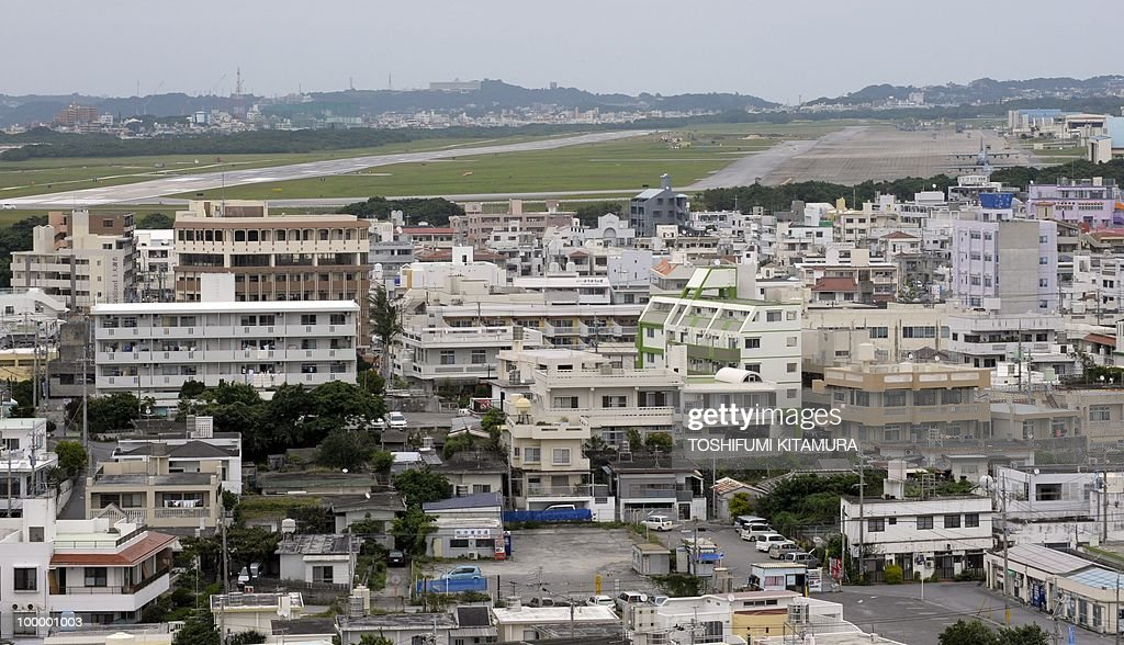 To go with feature story Japan-US-military-diplomacy by Kyoko Hasegawa A picture taken on April 26, 2010 shows residential houses located beside the US Marine Corps Air Station Futenma at Ginowan, Okinawa prefecture. The deafening US military jets sometimes fly so low that the pilots' faces are visible to the people living around their airbase on the southern Japanese island of Okinawa. The base has been there since the palm-fringed island emerged from the battles of Word War II to become Japan's main US military staging area -- but many locals say they'll never get used to the ear-splitting noise.