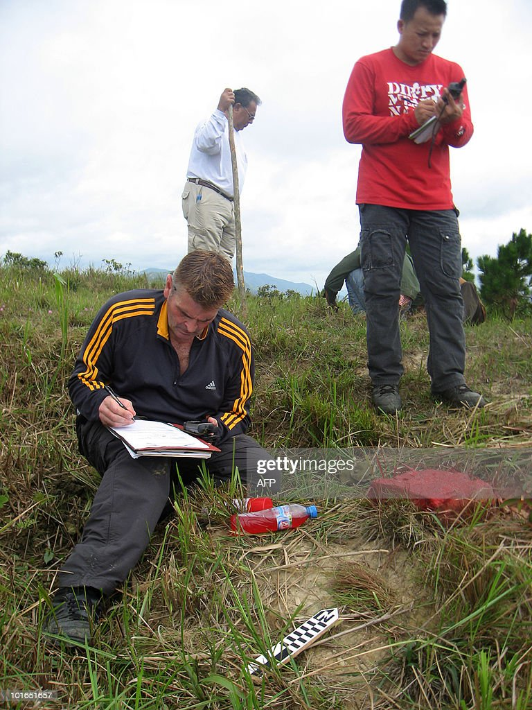 To go with feature story Vietnam-US-MIA-investigation by Ian Timberlake In a picture taken on May 30, 2010 Vietnam War veteran Al Maumausolo (C background) stands by as US Army Sergeant David White (L) makes notes on the edge of an overgrown bomb crater on Hill 881 South in Quang Tri province in Vietnam during a Joint POW/MIA Accounting Command (JPAC) search to find the remains of a missing US soldier from the Vietnam War. Maumausolo has returned to this mountain near the key Vietnam War battle site of Khe Sanh to help a group of United States military investigators led by White pinpoint the site where remains of a marine could be found. Since the end of US combat involvement in 1973, 655 Americans listed as missing during the war have been repatriated from Vietnam and identified but 1,313 remain unaccounted for, the US says.