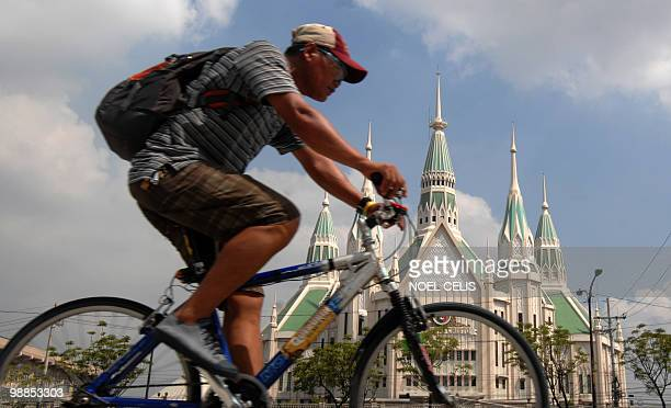 To go with focus story Philippinespoliticsvotereligion by Mynardo Macaraig A cyclist passes the 'Iglesia Ni Cristo' central temple in Quezon City a...