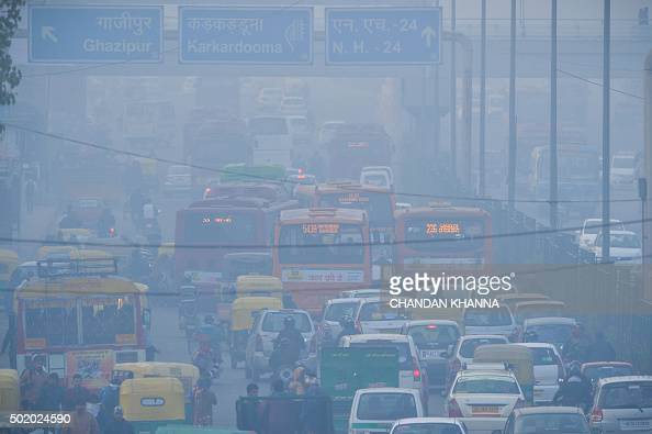 To go with IndiaenvironmentpollutionFOCUS by Trudy Harris In this photograph taken on December 18 Indian commuters travel on a polluted road near a...