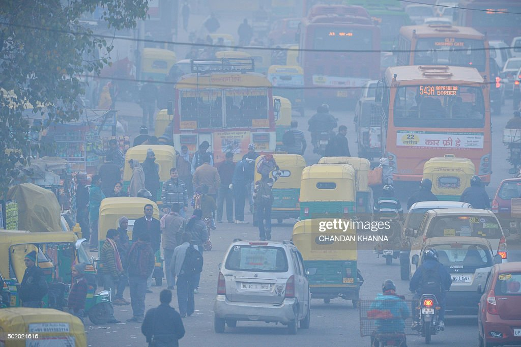 TOPSHOT To go with IndiaenvironmentpollutionFOCUS by Trudy Harris In this photograph taken on December 18 Indian commuters travel on a polluted road...