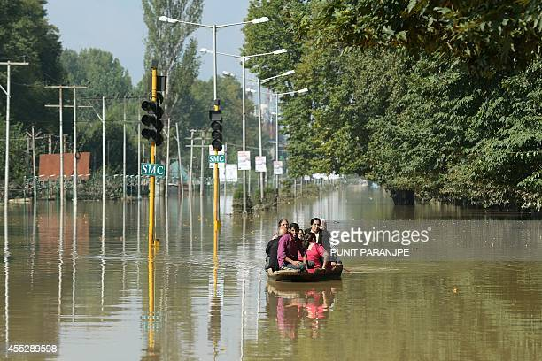 To go with IndiaPakistanKashmirfloodshikaraSCENE by Bhuvan BAGGA This photo taken on September 11 2014 shows Kashmiris riding a shikara boat over a...