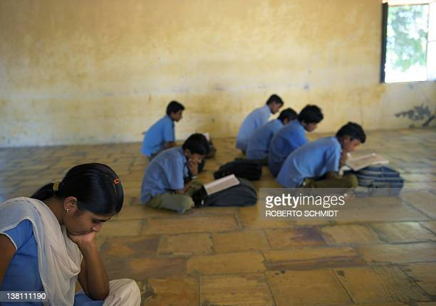 To go with INDIAWOMENCHILDRENCRIME by Rupam Nair This photo taken on November 15 2011 shows an Indian girl reading her book as she sits in a...
