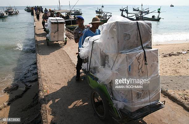 To go with Indonesiaelectionlogistics FOCUS by Arlina Arshad In this photograph taken on July 7 escorted by police Indonesian men transport on...
