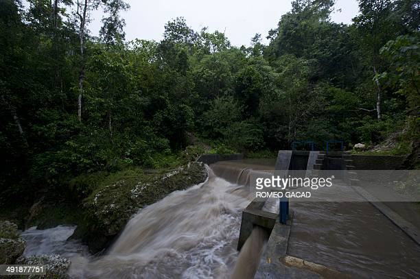 To go with Indonesiaenvironmentenergy FEATURE by Angela Dewan In this photograph taken on March 19 a dam is erected on a river powering a mini...