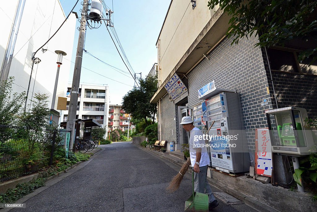 To go with Japan-Oly-2020-JPN,FOCUS by Shigemi SATO In this picture taken on September 14, 2013, 79-year-old resident Kohei Jinno sweeps and cleans a road before his apartment complex near the rebuilt national stadium in Tokyo. Tokyo's successful bid to host the Olympics made much of plans to re-use venues built for Japan's last Summer Games. But for Kohei Jinno, redevelopment for 2020 means eviction again, just like for 1964. In 1964, his home and business were torn down to make way for an Olympic park around the main stadium for the Tokyo Games. Now he has been told he must move again to make way for the stadium's redevelopment and expansion in time for 2020. AFP PHOTO / Yoshikazu TSUNO