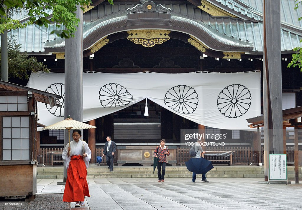 To go with Japan-politics-diplomacy-WWII-China-SKorea-Yasukuni,FOCUS by Hiroshi Hiyama In this picture taken on April 24, 2013, a shrine maiden (L) shelters under an umbrella as people visit the controversial Yasukuni shrine in Tokyo. For Japan's neighbours the leafy Yasukuni shrine is a brutal reminder of Tokyo's imperialist past and wartime aggression, but for many ordinary Japanese it is merely a place to worship ancestors who died fighting for the country. AFP PHOTO / Yoshikazu TSUNO