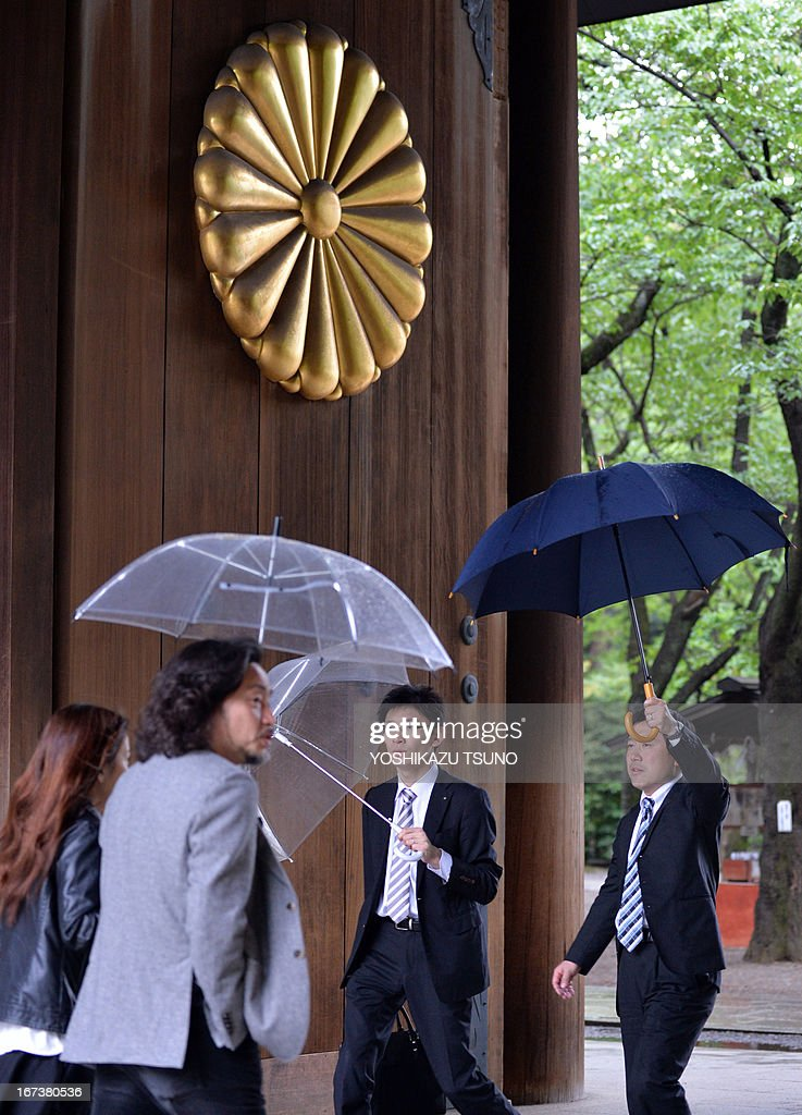 To go with Japan-politics-diplomacy-WWII-China-SKorea-Yasukuni,FOCUS by Hiroshi Hiyama In this picture taken on April 24, 2013, people visit the controversial Yasukuni shrine in Tokyo. For Japan's neighbours the leafy Yasukuni shrine is a brutal reminder of Tokyo's imperialist past and wartime aggression, but for many ordinary Japanese it is merely a place to worship ancestors who died fighting for the country. AFP PHOTO / Yoshikazu TSUNO