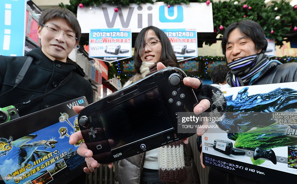 To go with 'Japan-US-game-entertainment-company-Nintendo,FOCUS' by Kyoko Hasegawa This picture taken on December 8, 2012 shows customers displaying their purchases after buying Japanese electronics titan Nintendo's new videogame console 'Wii U' at a shop. Nintendo is hoping its new Wii U console will catapult it back to pole position in the videogame sector, but analysts are divided on whether the Japanese gaming titan can reboot its fading glory. AFP PHOTO/Toru YAMANAKA