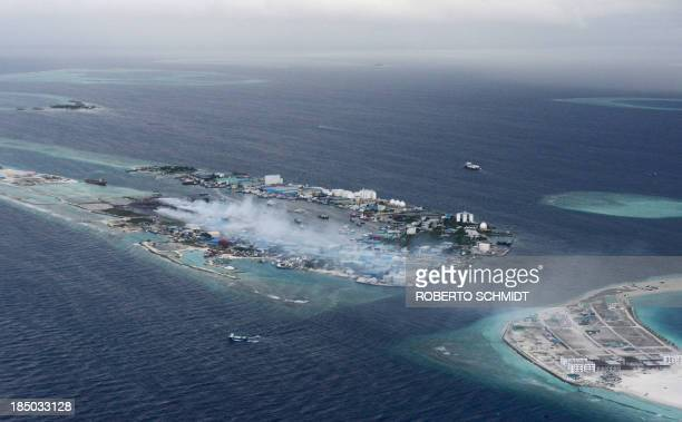 To go with MALDIVESENVIRONMENTWASTETOURISMFEATURE by ADAM In this photo taken on September 9 smoke billows from the Maldives's biggest trash dump...