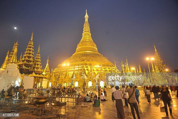 To go with MyanmarreligionheritagecultureFEATURE by HlaHla HTAY Devotees walk at the Shwedagon pagoda in Yangon on April 2 2015 As he smooths a gold...