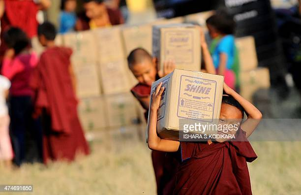 To go with NepalearthquakeeconomyaidFOCUS by Paavan MATHEMA In this photograph taken on May 22 a young Nepalese Buddhist monk carries relief...