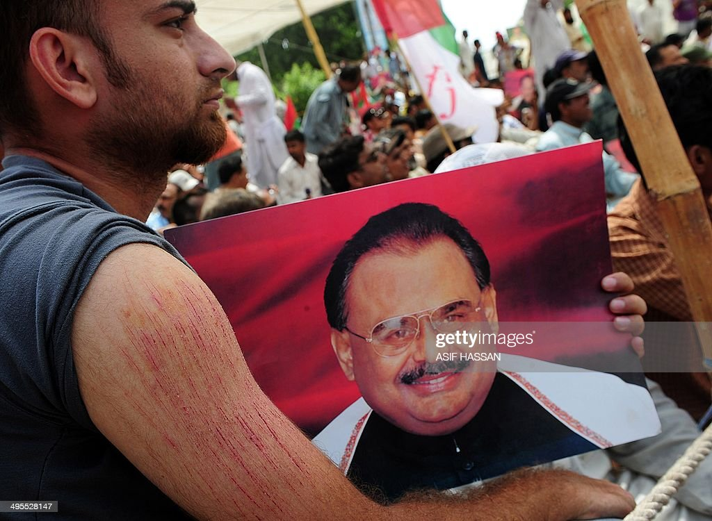 To go with Pakistan-Britain-Politics-MQM-Hussain,FOCUS by Ashraf KHAN Kashif Ahmed Shaikh , a supporter of Pakistan's Muttahida Qaumi Movement (MQM), holds a photograph of MQM party leader <a gi-track='captionPersonalityLinkClicked' href=/galleries/search?phrase=Altaf+Hussain+-+Muttahida+Qaumi+Movement&family=editorial&specificpeople=12871789 ng-click='$event.stopPropagation()'>Altaf Hussain</a> as razor blade cuts - self-inflicted in reaction to his leader's arrest - are seen on his forearm during a sit-in protest calling for Hussain's release in Karachi on June 4, 2014. For more than two decades, <a gi-track='captionPersonalityLinkClicked' href=/galleries/search?phrase=Altaf+Hussain+-+Muttahida+Qaumi+Movement&family=editorial&specificpeople=12871789 ng-click='$event.stopPropagation()'>Altaf Hussain</a> has wielded control of this freewheeling, violent city of 20 million half a world away from his drab London suburb home. The 60-year-old is revered by his fiercely loyal supporters -- mainly ethnic Mohajirs who migrated from India at the time of partition, while critics accuse him of running his party as a violent mafia-like organisation. AFP PHOTO/ Asif HASSAN