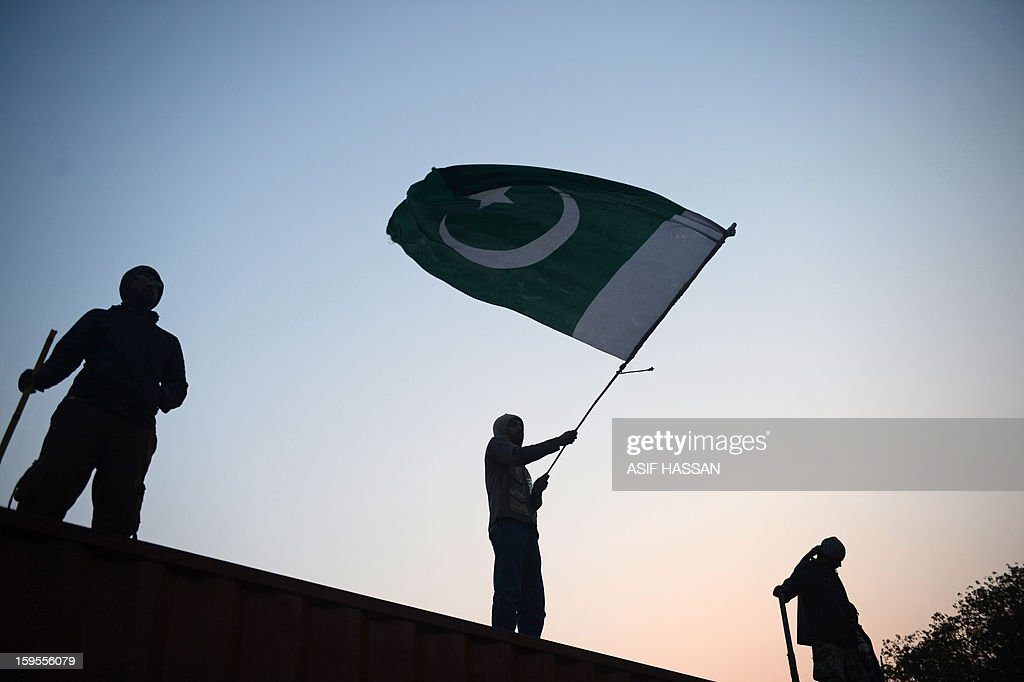 To go with Pakistan-unrest-politics-Islamabad,FOCUS by Nasir Jaffry A supporter of moderate preacher Tahir-ul Qadri waves this Pakistani national flag on the third day of a protest rally in Islamabad on January 16, 2013. An estimated 25,000 to 50,000 people have poured into Islamabad from across the country, devoted followers of moderate preacher Tahir-ul Qadri who is calling for the government to step down and radical reforms. It is the largest protest in the capital since the Pakistan People's Party won elections in 2008, ending a decade of military rule and forming what in March will be the country's first civilian government to complete a term in office. AFP PHOTO/Asif HASSAN