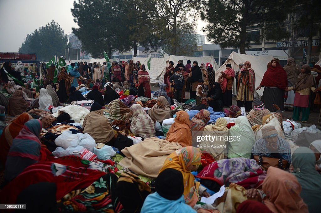 To go with Pakistan-unrest-politics-Islamabad,FOCUS by Nasir Jaffry Supporters of moderate preacher Tahir-ul Qadri gather and rest with their blankets at dawn on the third day of a protest rally in Islamabad on January 16, 2013. An estimated 25,000 to 50,000 people have poured into Islamabad from across the country, devoted followers of moderate preacher Tahir-ul Qadri who is calling for the government to step down and radical reforms. It is the largest protest in the capital since the Pakistan People's Party won elections in 2008, ending a decade of military rule and forming what in March will be the country's first civilian government to complete a term in office. AFP PHOTO/Asif HASSAN