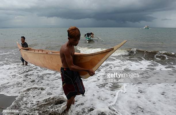 To go with PHILIPPINESTYPHOONCLIMATE Focus by Ted Aljibe This photo taken on November 1 2015 shows workers carrying a newlymade wooden boat to be...