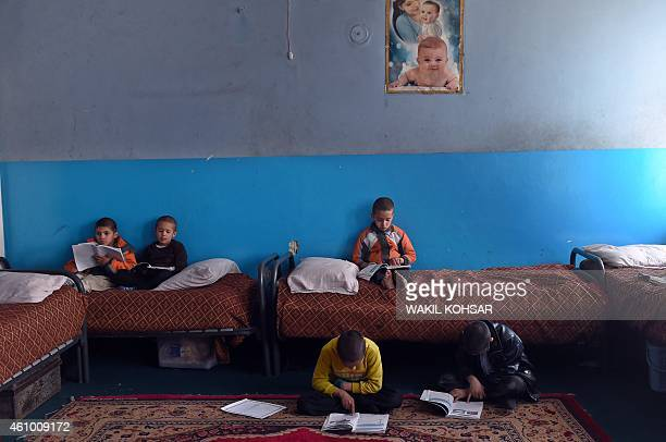 To go with story 'AfghanistanunrestchildrenorphanageFOCUS' by Emmanuel PARISSE In this photograph taken on December 17 Afghan children read their...
