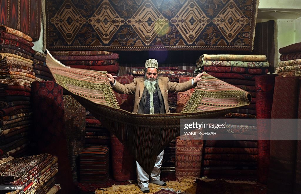 To go with story 'Afghanistan-unrest-social,FOCUS' by Ben Sheppard In this photograph taken on December 7, 2014, Afghan carpet trader Haji Abdull Hakim displays a carpet as he waits for customers in his shop on Chicken Street in Kabul. The tennis club is deserted, the Thai restaurant is closed and lakeside picnics are cancelled. The US-led war in Afghanistan brought a flood of international aid workers, diplomats and security contractors to Kabul, creating a frenetic social scene that is now a distant dream. A series of Taliban attacks on expat hang-outs shattered any illusions that foreign civilians were safe in the city, and those places still open have bored waiters and empty tables. As the United States and its allies officially end their 13-year war on December 31, Afghanistan appears in the grip of worsening violence, and the remaining foreign workers have retreated further inside fortified compounds. AFP PHOTO/Wakil Kohsar
