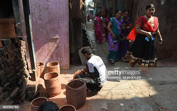 IndiaartsocietyhealthFOCUS by Rachel O'Brien In this photograph taken on February 11 2015 residents walk past a potter sanding a pot behind the...