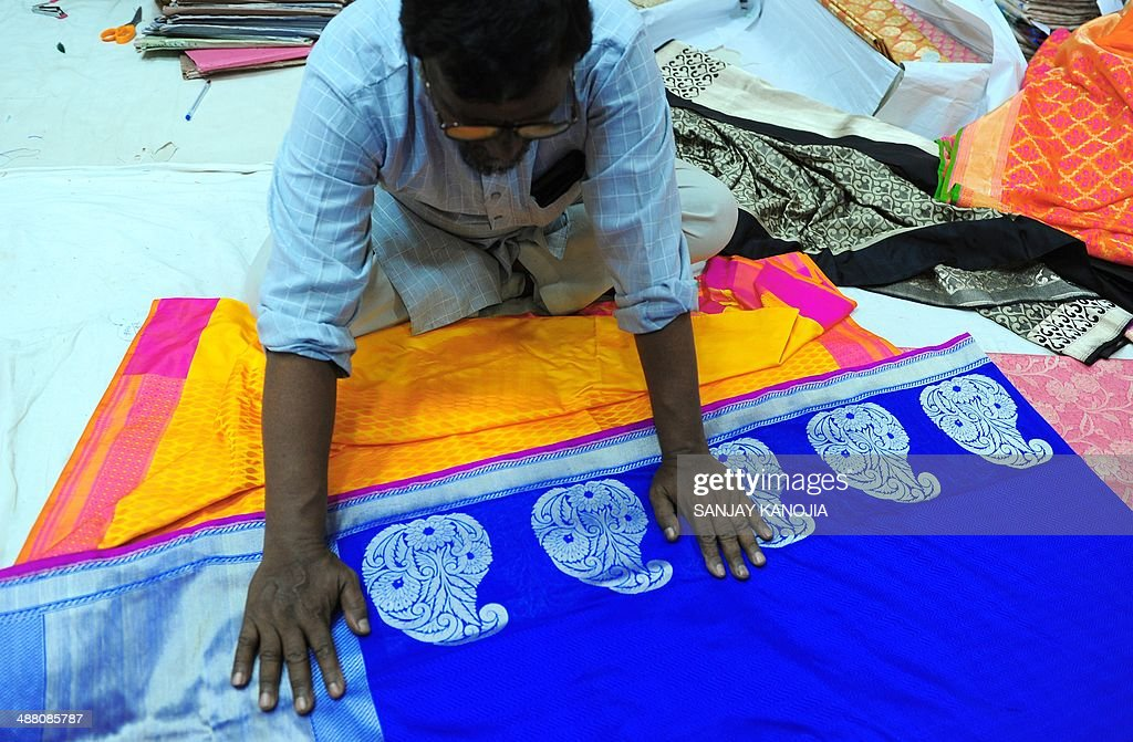 To go with story IndiaelectioneconomytextileFEATURE by Bhuvan BHAGGA In this photograph taken on April 22 2014 an Indian shopkeeper displays the...