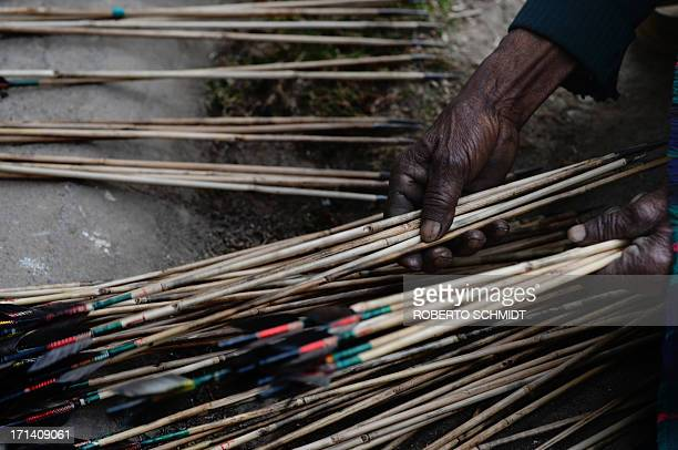To go with story 'Indiagamblingarcherytradition' In this photograph taken on February 2 2013 an Indian man arranges arrows by the color of their...