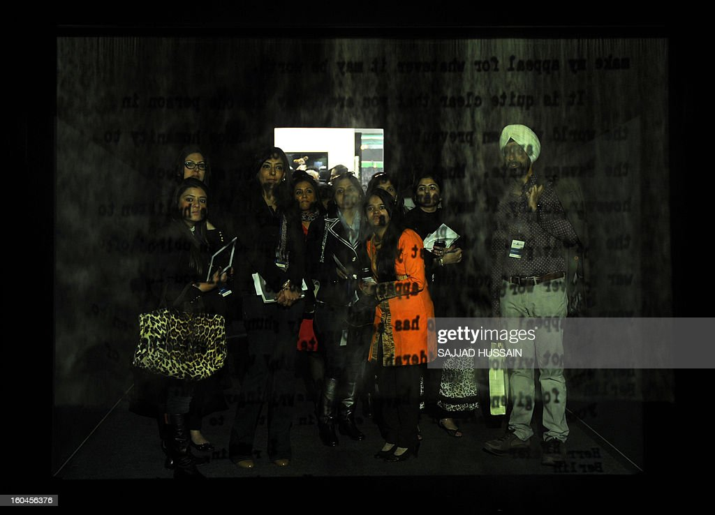 To go with story 'Lifestyle-India-art-business' by Penny MacRae Visitors look at a FogScreen projection displayed at the India Art Fair in New Delhi on January 31, 2013. India's art world has converged on New Delhi for the industry's biggest annual event where upbeat talk and parties are likely to disguise a market that is still in the doldrums since its 2008 crash.