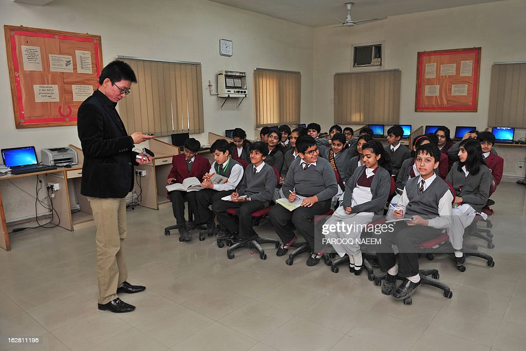 To go with story Pakistan-Chine-société-économie-éducation,PREV by Guillaume LAVALLEE In this picture taken February 18, 2013, Pakistani schoolchildren learn Chinese from their teacher Mr. Haiwei in the private City School in Islamabad. While the country's elite continue to look westward for their children's education, an emerging Pakistani middle class is turning towards its prospering neighbour China as a more affordable means to receive quality education, with private schools and universities in Pakistan providing progammes in the language. AFP PHOTO/Farooq NAEEM