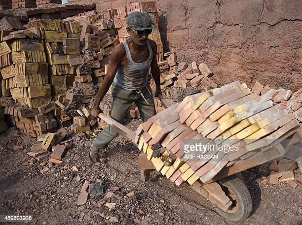 To go with story 'PakistanLabourRightsSlavery' by Guillaume Lavallee In this photograph taken on November 10 2014 a Pakistani labourer uses a trolley...
