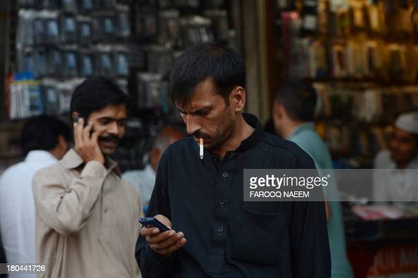 To go with story 'PAKISTANTELECOMMUNICATIONYOUTHSOCIETY'' by Masroor GILANI In this photograph taken on September 10 a Pakistani man checks messages...