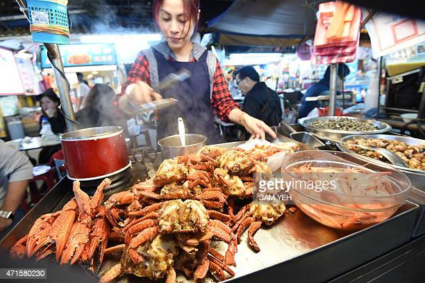 To go with Taiwanfoodlifestyledesign FEATURE by Laura MANNERING In this photo taken on April 13 a local chef prepares food at the Raohe night market...