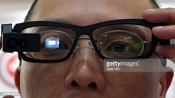 To go with TaiwanlifestyletechnologywearablesComputexFOCUS by Laura Mannering This picture taken on June 2 2015 shows a man operating smart glasses...