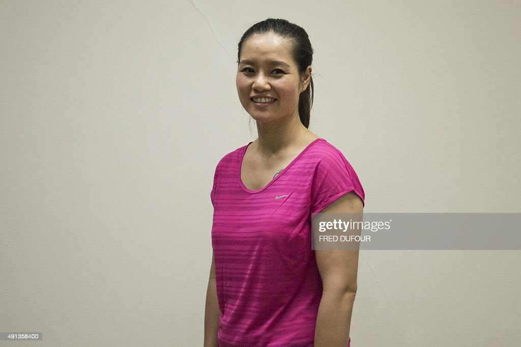 To go with Tennis-CHN-China-Li,FOCUS by Annanel Symington In this photo taken on September 29, 2015, former tennis player Li Na of China poses on the sidelines of the women's singles final at the Wuhan Open tennis tournament in Wuhan, central China's Hubei province. Li Na's Grand Slam wins did miraculous things for tennis in China but a cultural shift away from central planning towards individual development is needed if the country is to emerge as a powerhouse, experts say. AFP PHOTO / FRED DUFOUR