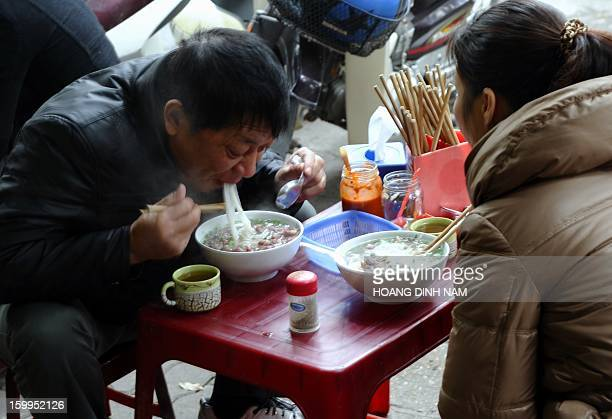 To go with 'VietnamfoodcultureFEATURE' by Cat Barton This picture taken on January 11 2013 shows people eating pho noodle soup in front of a pho...