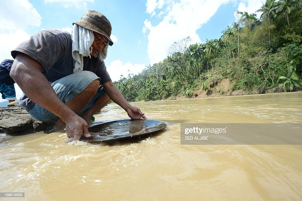 To go with 'Weather-Philippines-typhoon-mining-environment,FOCUS' by Mynardo Macaraig A miner pans for gold at a river near the typhoon disaster zone in Mawab town, compostela valley province on December 9, 2012. Unchecked illegal gold mining and decades of indiscriminate logging contributed to the high death toll in the Philippines' worst natural disaster this year, officials and experts say.