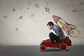 The portrait of a young Asian guy in a red toy car in front of a gray wall with spaceship and planets.