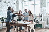 Group of happy business people toasting each other and smiling while standing in the board room