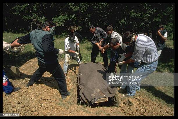 To prevent the spread of disease men wear masks as they bury the body of a victim killed in Kosovo during the Yugoslavian Civil War In the 1990s the...