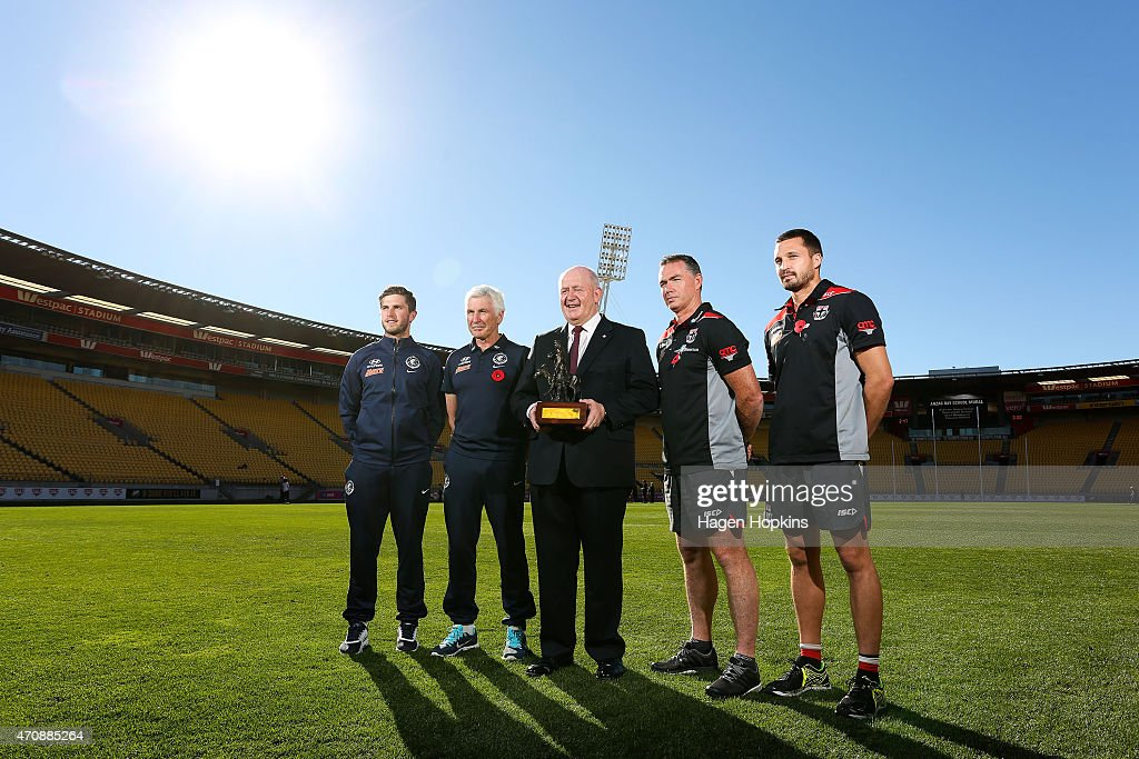 L to R, Captain Marc Murphy and coach Mick Malthouse of Carlton, Australian Governor-General Sir Peter Cosgrove, coach Alan Richardson and captain Jarryn Geary of St Kilda pose with The Simpson-Henderson Trophy after team training sessions at Westpac Stadium on April 24, 2015 in Wellington, New Zealand.