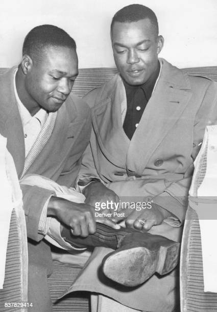 L to R Hank Thompson Monte Irvin Monte Irvin slugging outfielder of the New York Giants shows hid bad ankle to teammate Hank Thompson as the big...
