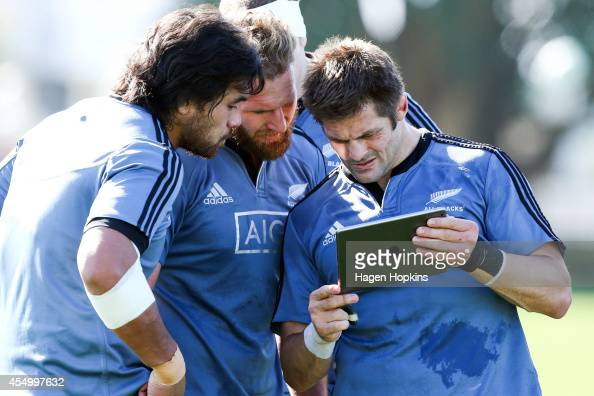 L to R Steven Luatua Kieran Read and Richie McCaw look at an iPad during a New Zealand All Blacks training session at Hutt Recreation Ground on...