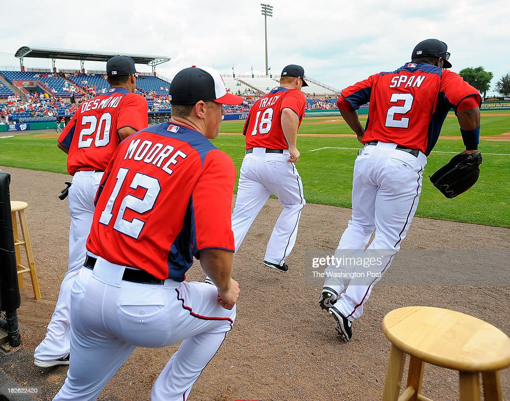 Washington shortstop Ian Desmond (20), Washington right fielder Tyler Moore (12), Washington first baseman Chad Tracy (18) and Washington center fielder Denard Span (2) spring out of the dugout and onto the field as the Florida Marlins tie the Washington Nationals 2 -2 in 10 innings during Grapefruit League baseball in Viera FL, February 24, 2012 .