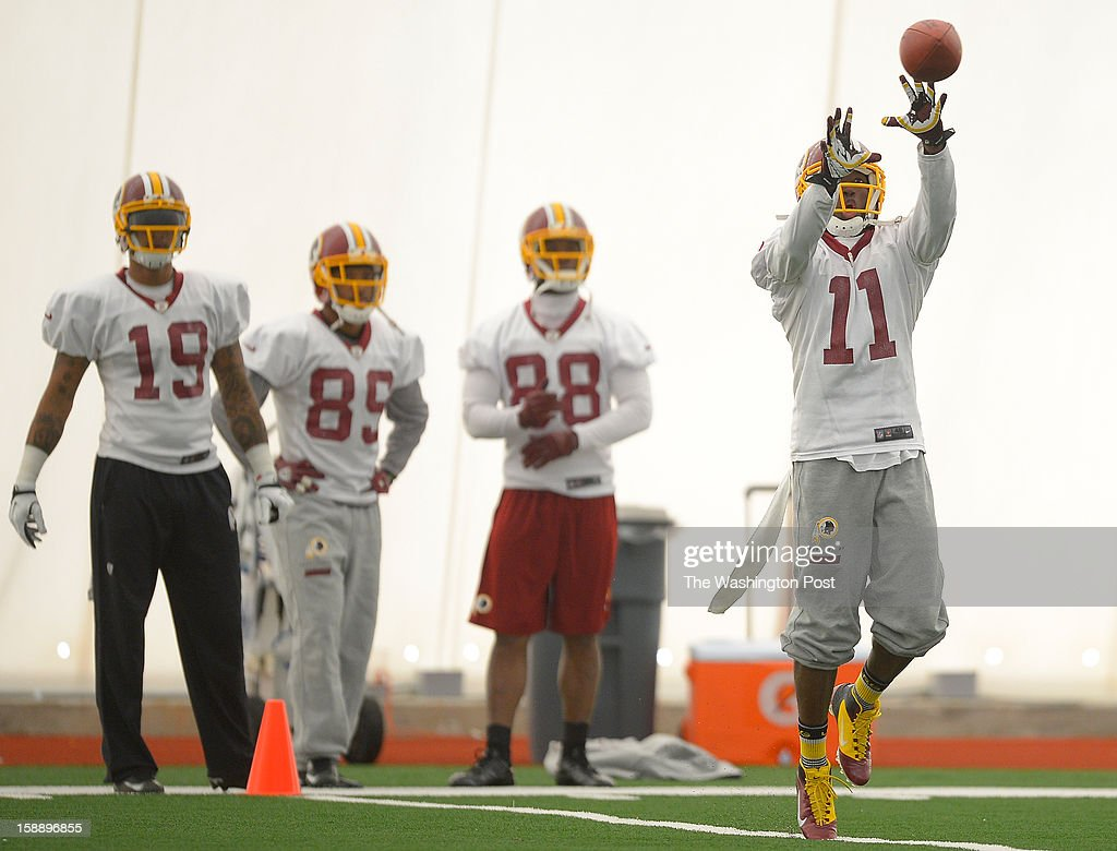 Washington wide receivers Dezmon Briscoe (19), Santana Moss (89), Pierre Garcon (88) watch Aldrick Robinson (11) make a catch during drills as the Washington Redskins practice for the upcoming playoff game against the Seattle Seahawks in their indoor practice facility at Redskins Park in Ashburn VA, January 2, 2012 .