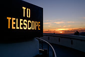Sign at the Griffith Observatory in Los Angeles, looking out over the dusk sky.