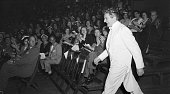 To the obvious delight of his female fans Liberace the pianist resplendent in white silk tails makes his entrance for his May 26th concert at Madison...