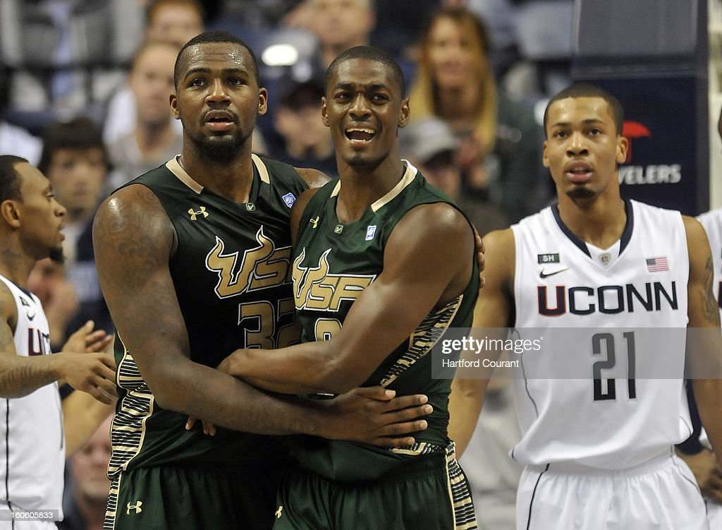 Toarlyn Fitzpatrick, left, and Victor Rudd of the South Florida Bulls celebrate the team's strong first-half performance against the Connecticut Huskies at Gampel Pavilion in Storrs, Connecticut, Sunday, February 3, 2013.