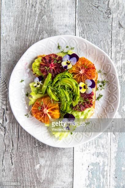 Toast garnished with iceberg salad, avocado, sliced blood orange, cress and horned violets
